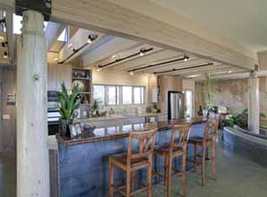 Well-lit kitchen with breakfast bar in a poured earth home located in Prescott, AZ